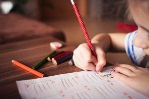 Niña pequeña escribiendo una carta con regalos