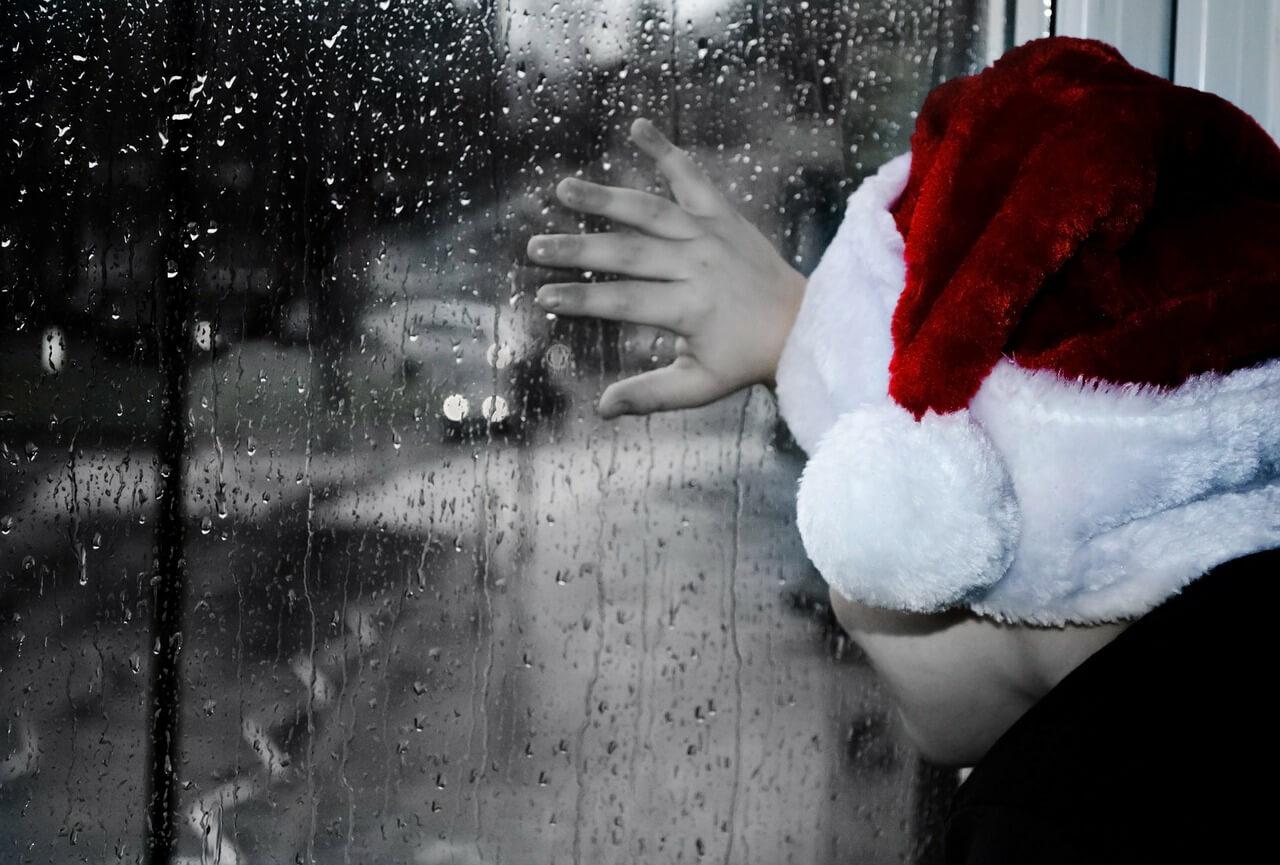 niño con gorro de navidad en una ventana