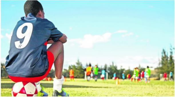 niño sentado en una pelota en una prueba de fútbol - Football Trials for European Soccer | Ertheo Sports and Education