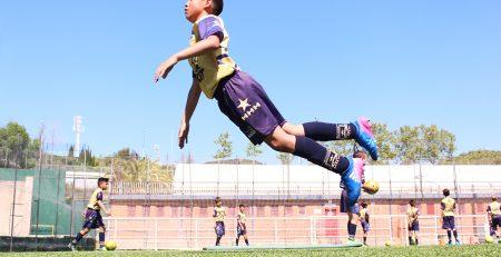 jugador de la academia de fútbol en Barcelona rematando de cabeza