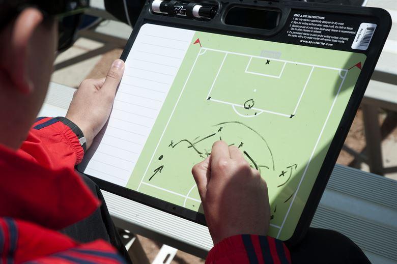 entrenador de fútbol escribiendo en su pizarra